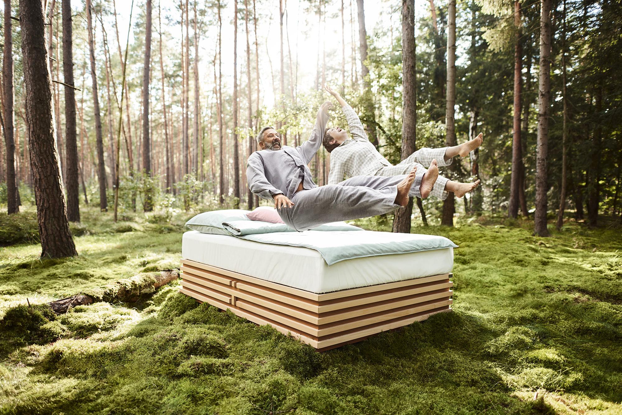 Best Ager Paar springt auf eine stylische Matratze in der Natur
