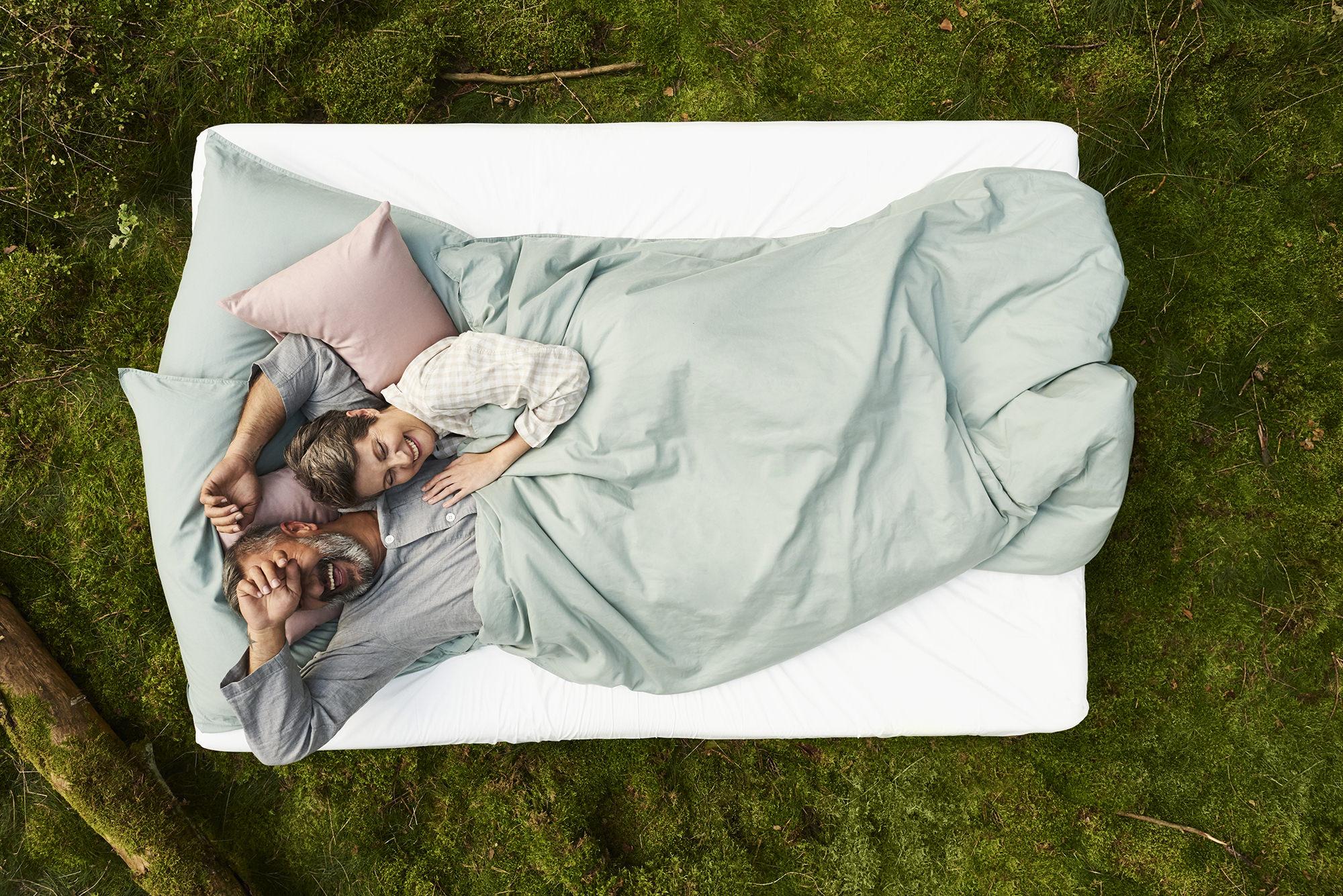 Best Ager Paar liegt auf einer stylischen Matratze in der Natur und kuschelt