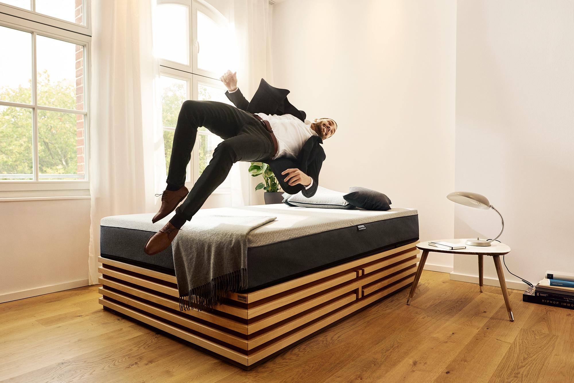 Business Mann springt auf eine stylische Matratze