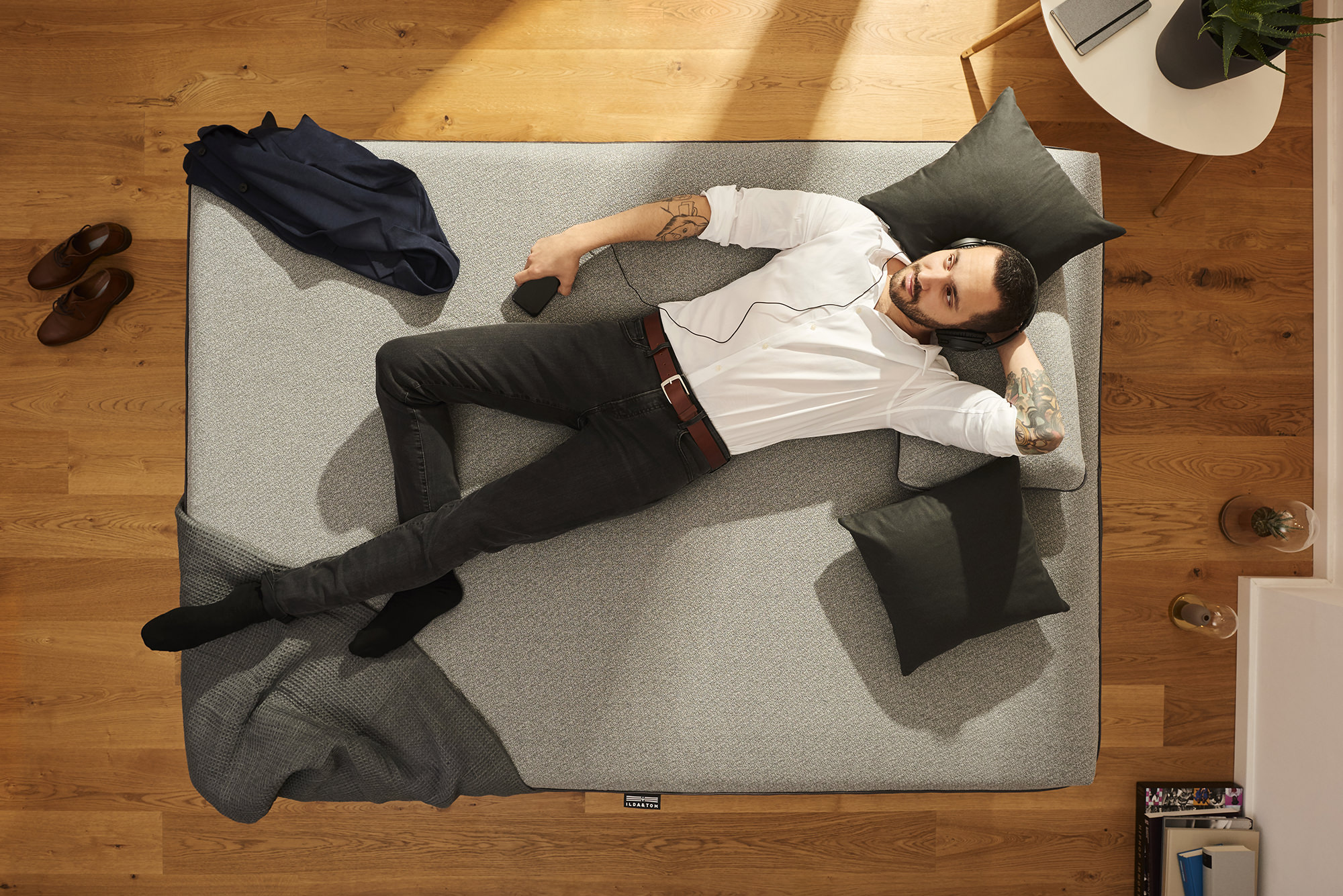 Business Mann chillt auf einer stylischen Matratze und hört Musik