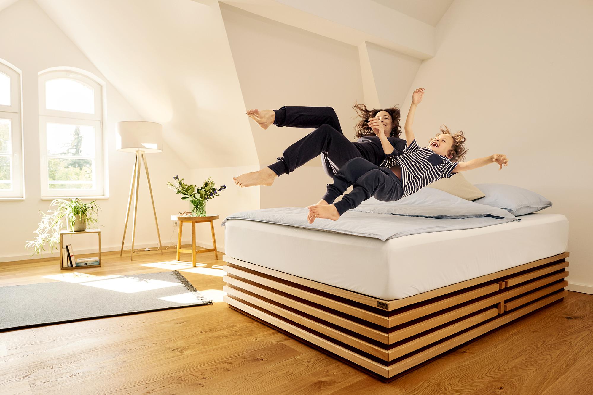 Mutter und Kind springen auf eine stylische Matratze