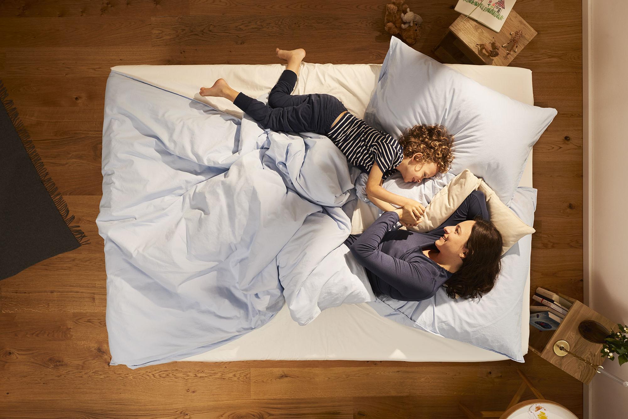 Mutter und Kind kuscheln auf einer stylische Matratze