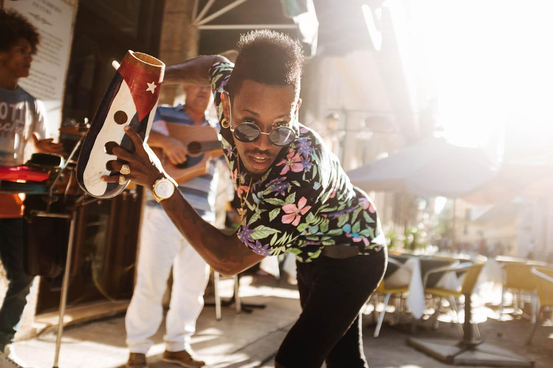 Straßenmusiker tanzt mit Instrument Kuba